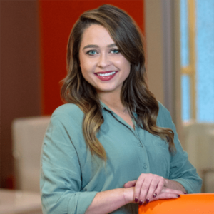 A businesswoman smiling at the camera resting her hands atop an orange chair wearing red lipstick and an emerald green button up shirt