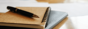 A pen resting on top of a tan, spiral notebook resting on top of a black binder all laying flat on a wooden table