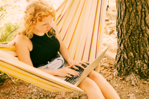 A millennial sitting on top of a hammock connected to a tree as she browses on her macbook pro outside