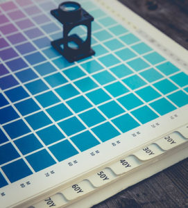 Different pantones from purple to blue laid out on a sheet with a magnifying glass