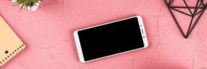 An android cell phone surrounded by office supplies resting atop a pink plastered background