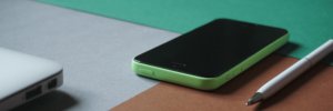 A linear view of a Microsoft phone next to a white pen resting adjacent to the corner of a laptop and the background of the surface is aqua-green on top, grey to the left, and tan to the right creating a trifecta background effect