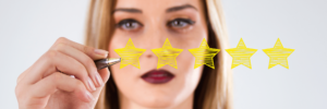 The face of a woman wearing red-rose lipstick holding a pen, drawing yellow scribbled in stars, five in total