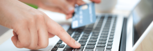 A person typing on a laptop with their right index finger on the return key probably purchasing a product or service and in the other hand his bank debit card