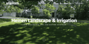 A screenshot of the home page slider for Heinen Landscape Kansas City Irrigation and Sprinklers with a residential, white Victorian home