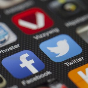 Facebook and Twitter apps on the front screen of a phone