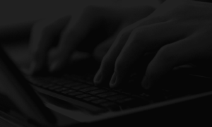 A person typing keys on a keyboard zoomed in and a dark overlay over the entire image