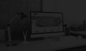 An image of a Mac Book Pro with Minsky's Pizza pulled onto a window sitting atop a desk surrounded with office supplies and a dark overlay over the entire image